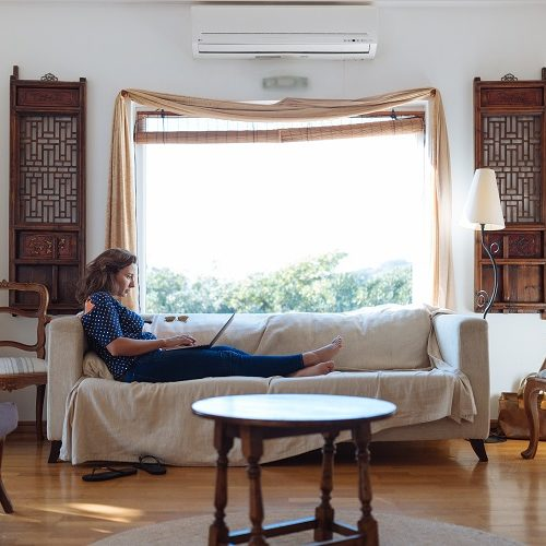 Canva-Woman-Sitting-on-Sofa-in-Living-Room_
